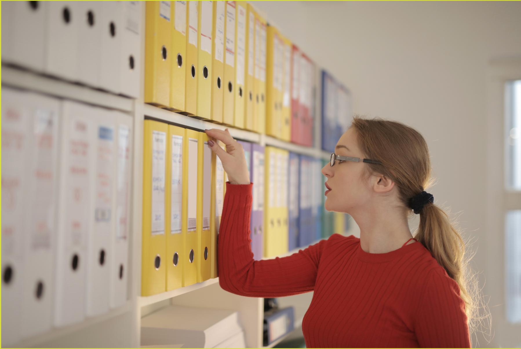 kobieta stoi przy półkach z segregatorami i szuka dokumentów